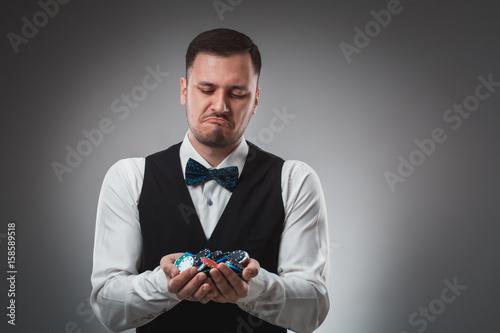 Young man in shirt and waistcoat shows his poker chips, studio shot плакат