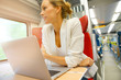 Businesswoman in train connected on laptop computer - 158627100
