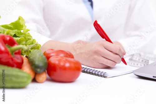 Foto Murales Vegetable diet nutrition or medicaments concept. Doctors hands writing diet plan, ripe vegetable composition, laptop and measuring tape on white background