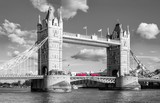 tower bridge with traditional red bus in black and white colors in london