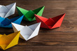 Quadro Business leadership concept with white and color paper boats on wooden table