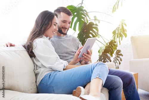 Lovely pair sitting on sofa and surfing in tablet