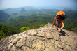 young woman climber climbing rock at mountain top