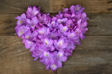 pink rhododendron heart bouquet on rustic wood