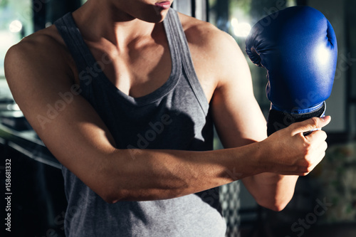 Staande foto Young athletic man with boxing glove in fitness gym.