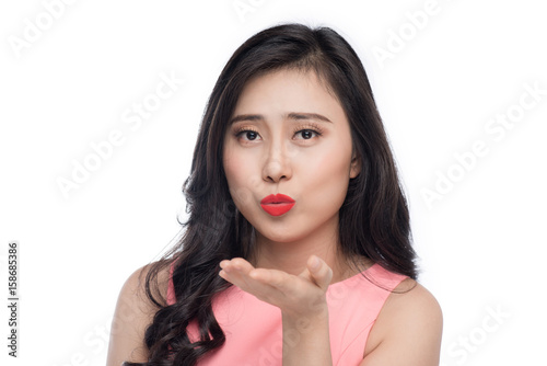 Asian young beautiful woman in pink dress blowing over white. Poster
