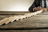 Businessman interrupting domino effect - 158699950