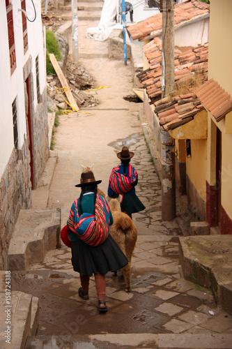 Péruvienne et lama dans une ruelle de Cusco au Pérou
