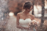 Bride with a bouquet of flowers in a white dress at a wedding - 158732708