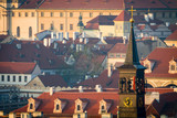 Roofs and clock tower old town of Prague in morning orange light.