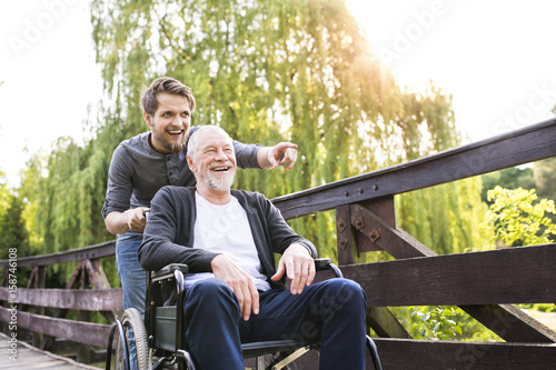 Leinwandbild Motiv Hipster son walking with disabled father in wheelchair at park.