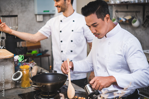 Wall mural chef preparing food in the kitchen of a restaurant