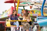 Two teenage girls having fun on an amusement park ride