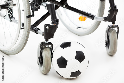 Wheelchair for invalid or disabled person and soccer ball - 158795517