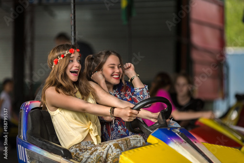 Poster Amusementspark Two young girlfriends are laughing and shouting while riding a bumper car at amusement park
