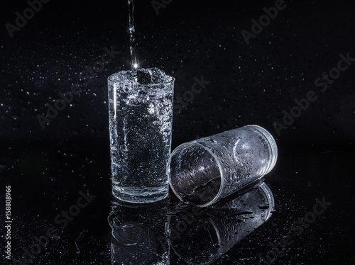 Water splash and crystal glass on black background.
