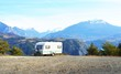 Caravan with a bike parked on a mountaintop with a view on the french Alps near lake Lac de Serre-Poncon on a bright sunny day