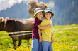 Happy children walking on a rural path in Swiss Alps, springtime