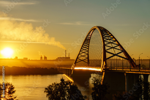 Bridge over river in the city at spectacular sunrise in the background