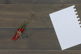red chili pepper and paper note on wooden table with free text space