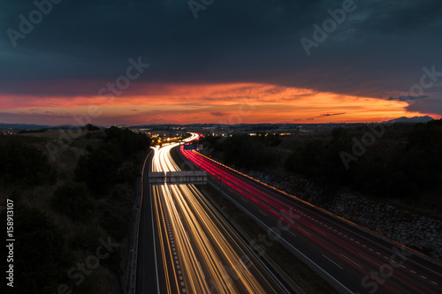 Foto op Canvas Nacht snelweg Highway Traffic Light Trails and Sunset
