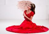 Beautiful elegant girl in a long red dress and shoes sits on the floor with an old vintage umbrella in a white room