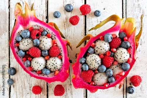 Colorful dragon fruit salads with raspberries and blueberries over a white wood Poster
