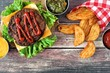 Picnic scene with barbecued hamburger and potato wedges over dark rustic wood
