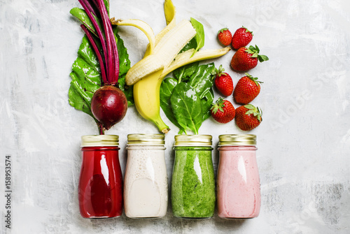 Multicolored juices and smoothies of fresh vegetables, fruits and berries, top view, food background