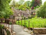 Old footbridge and  traditional Cotswold cottages,   Bibury,  England, UK. - 158954770