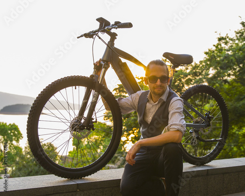 man next to electric bike with sunset