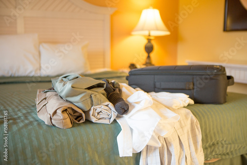 Mens clothes on a bed in a hotel room