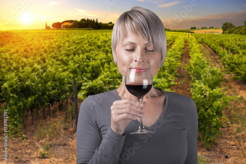 Portrait of young brunette beauty in the vineyards having wine. Poster