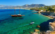 ship like pirate schooners with two masts for sails near rocks of the coast of Crete