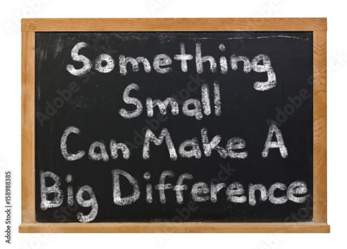 Something small can make a big difference written in white chalk on a black chalkboard isolated on white