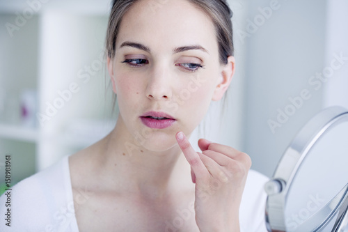 Woman looking at herself in the mirror Poster