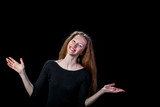 Joyful young brown-haired girl spread her hands to the sides on a black background