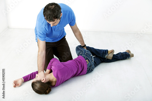 First aid techniques : placing the victim in the recovery position Step 4 : roll the victim by pulling on their leg until their knee touches the ground Remove your hand from the victim's head, holding their elbow so their hand stays in place