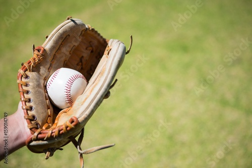 Cropped hand of baseball pitcher holding ball in glove Poster