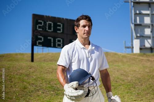Cricket player holding helmet on field