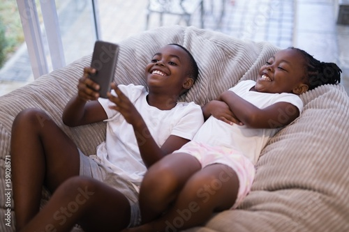 Happy siblings using mobile phone while lying on couch