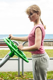 Active woman exercising with tai chi wheel.