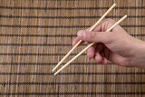 chopsticks in hand on the background of a sushi mat