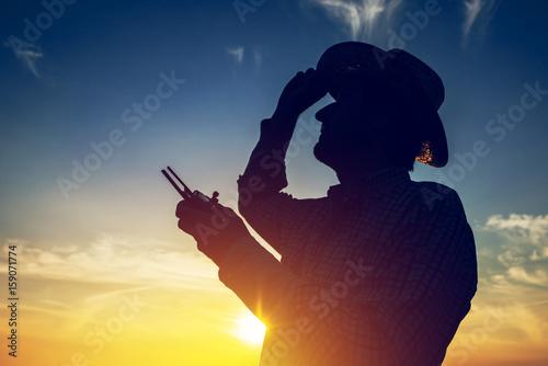 Silhouette of farmer using drone remote control Poster
