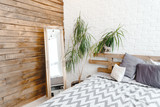 Light studio interior with mirror in the corner, plant in vase and pallets bed - 159073569
