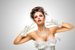 Glamorous gesture / Sexy pinup bride in a vintage wedding corset showing V sign on grey background.