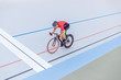 Cyclist finishes on velodrome. Professional athlete in a red T-shirt and a black bicycle.