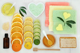 Citrus spa beauty treatment products with orange, lemon and lime fruit, bath crystals, essence, sponge, honey, almond oil, soap with flannels on rustic wood background.