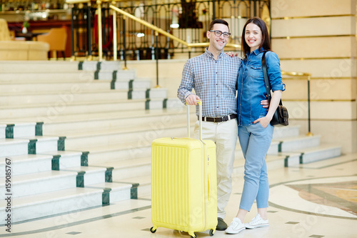 Happy young couple of travelers with suitcase