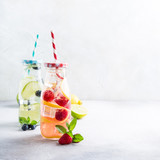 Two glass bottles with lemonade from fresh citrus lemon, raspberries, blueberries, lime and mint with drinking straws. Healthy summer beverage. Copy space, selective focus.